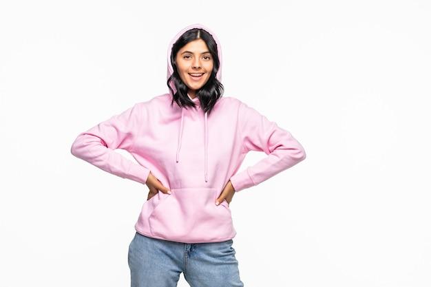 Retrato de una mujer joven con una sudadera con capucha posando aislado en la pared blanca