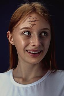 Retrato de mujer joven superando problemas de salud mental. tatuaje en la frente con las palabras te amo a mí mismo.