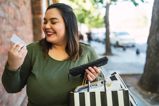 Retrato de mujer joven de talla grande sosteniendo una tarjeta de crédito y bolsas de compras al aire libre en la calle. concepto de compra y venta.