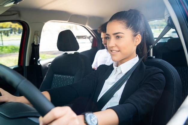 Retrato de mujer joven taxista con un pasajero empresario en el asiento trasero