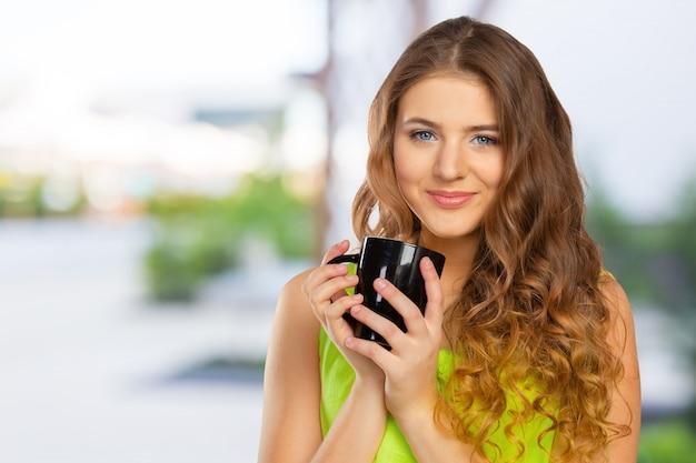 Retrato de una mujer joven con una taza de té o café