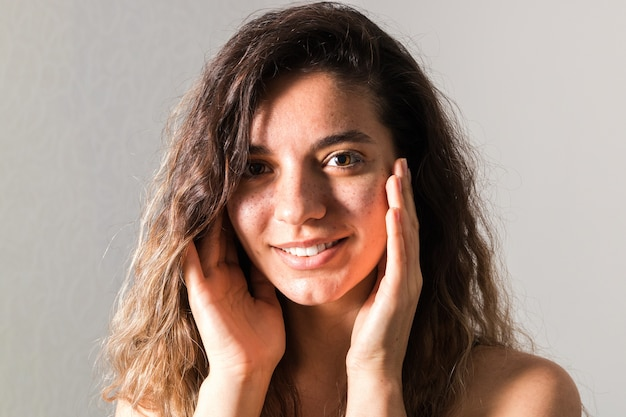Retrato de mujer joven tierna con pelos rizados sonriendo y tocando su rostro contra el fondo azul.