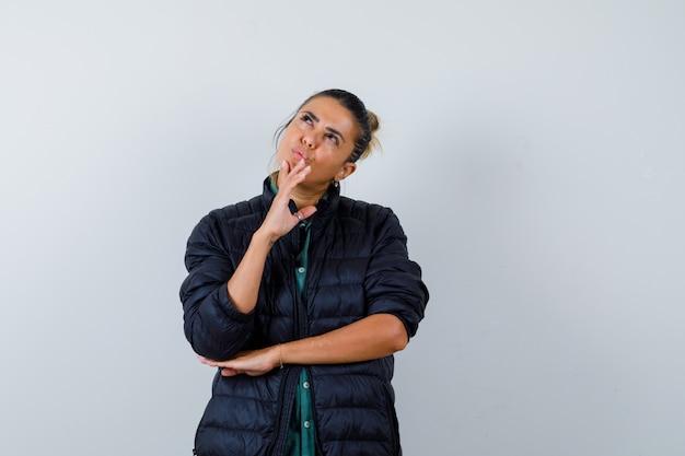 Retrato de mujer joven tocando la barbilla mientras mira hacia arriba en chaqueta acolchada y mirando pensativo vista frontal
