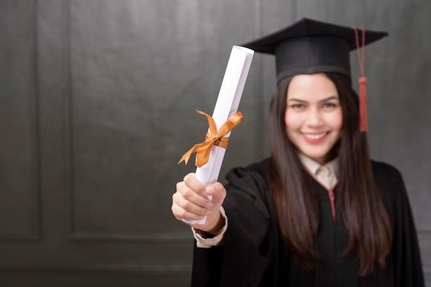 Retrato de mujer joven en toga de graduación sonriendo y animando sobre fondo negro