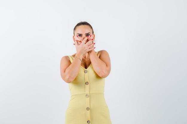Retrato de mujer joven tomados de la mano en la boca con vestido amarillo y mirando asustado vista frontal