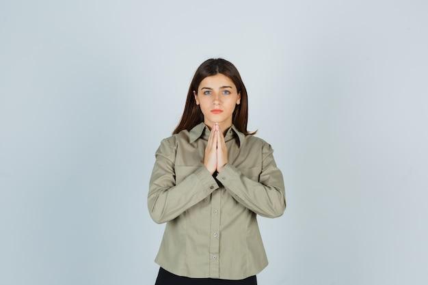Retrato de mujer joven tomados de la mano en gesto de oración en camisa, falda y mirando esperanzada vista frontal