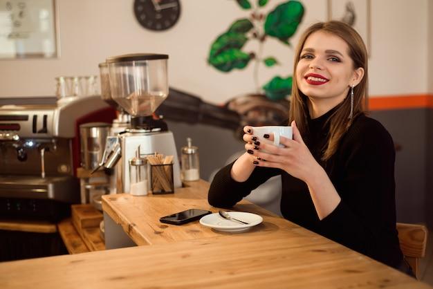 Retrato de mujer joven tomando café en la cafetería.