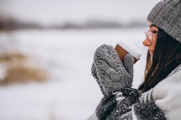 Retrato de mujer joven tomando café en un parque de invierno