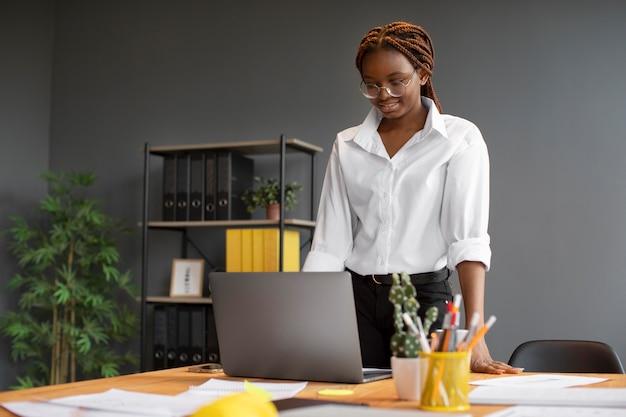 Retrato de mujer joven trabajando en su computadora portátil en una empresa de nueva creación