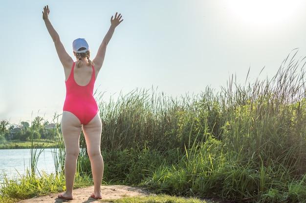 Retrato de una mujer joven en traje de baño en la playa de pie de espaldas con las manos sobre la cabeza. concepto cuerpo positivo