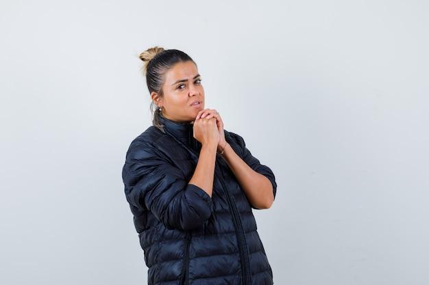 Retrato de mujer joven uniendo las manos en gesto de oración en chaqueta acolchada y mirando esperanzado vista frontal