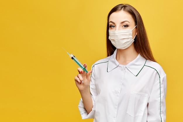 Retrato de mujer joven en uniforme médico y máscara protectora con jeringa médica en mano