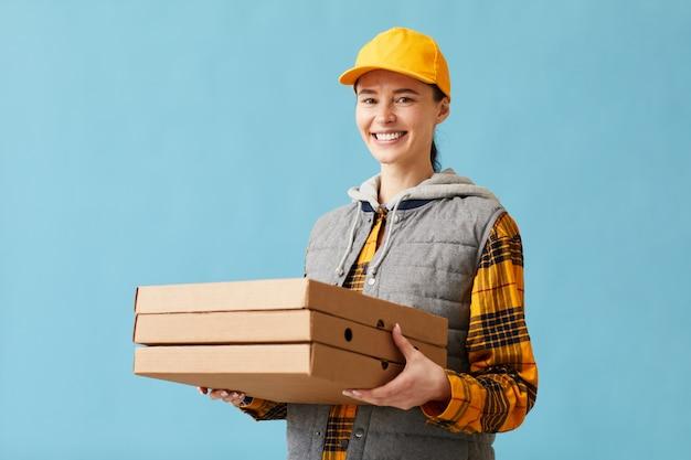 Retrato de mujer joven en uniforme sonriendo a la cámara y entregando pizza ella de pie contra el fondo azul.