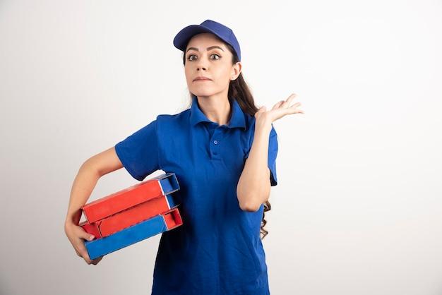 Retrato de mujer joven en uniforme sonriendo y repartiendo pizza. foto de alta calidad