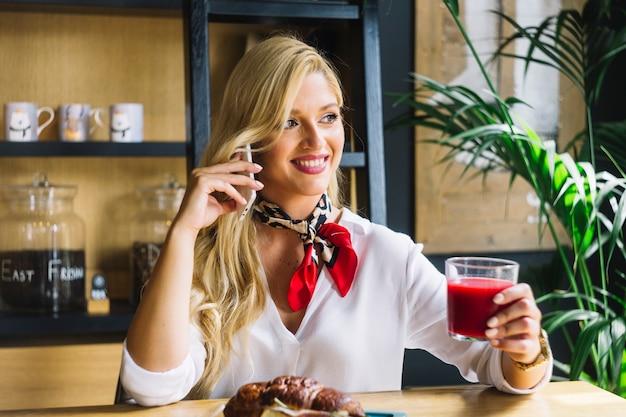 Retrato de una mujer joven con vaso de jugo hablando por teléfono celular