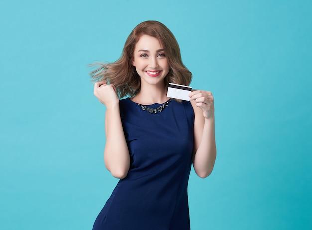 Retrato de una mujer joven en vestido azul mostrando tarjeta de crédito y mirando