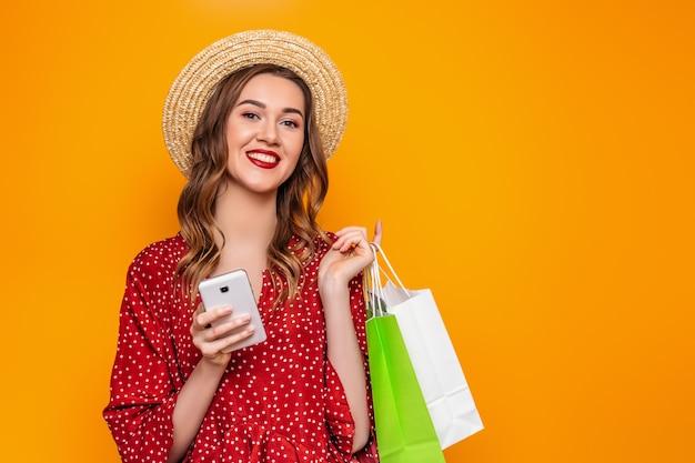 Retrato de una mujer joven en un vestido rojo de verano sombrero de paja tiene un teléfono móvil en sus manos aisladas sobre banner de web de pared amarilla. chica hace compras en línea de compras