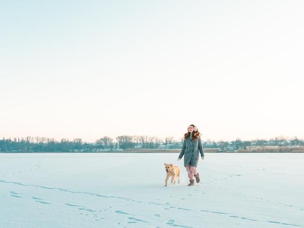 Retrato mujer joven en winter park caminando con su perro golden retriever. amistad, mascota y humano.