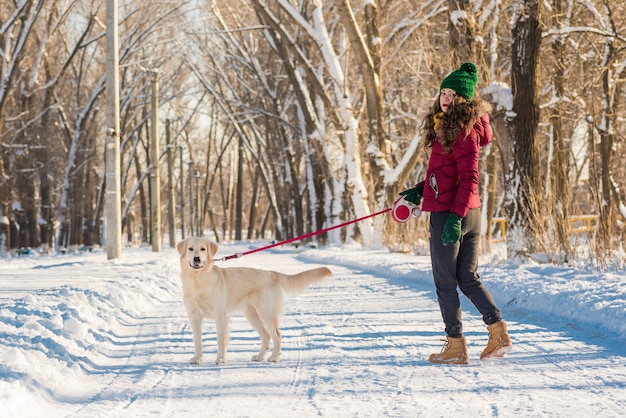 Retrato de mujer joven en winter park caminando con su perro golden retriever