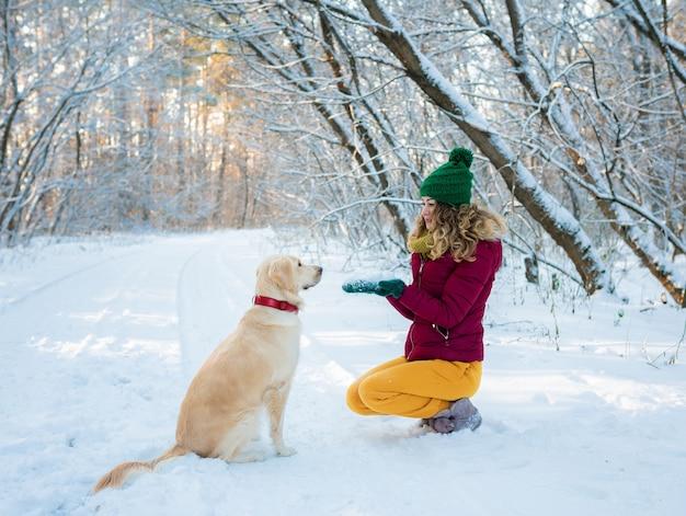 Retrato de mujer joven en winter park jugando con su perro
