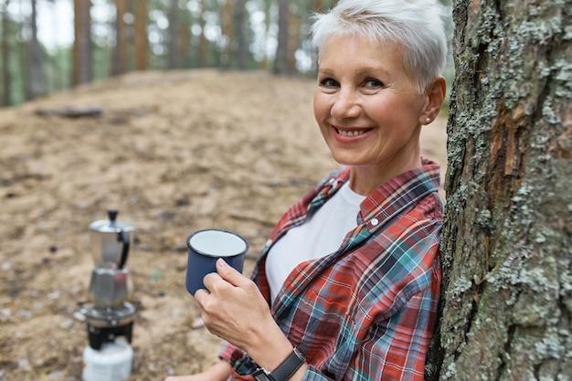 Retrato de mujer jubilada enérgica recostada sobre pino sosteniendo una taza, bebiendo té ella del agua que ella hirvió en la tetera en el quemador de camping