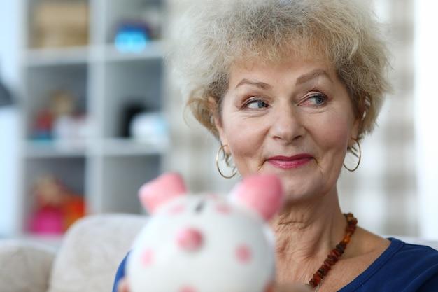 Retrato de mujer jubilada sonriente sosteniendo hucha hucha