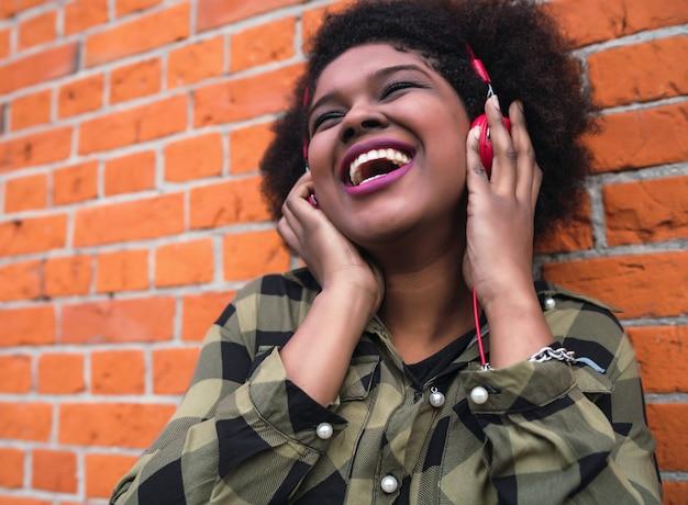 Retrato de mujer latina afroamericana sonriendo y escuchando música con auriculares contra la pared de ladrillo. al aire libre.