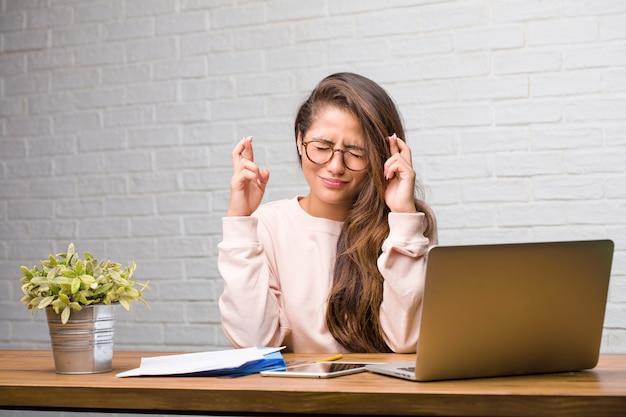 Retrato de la mujer latina del estudiante joven que se sienta en su escritorio que cruza sus fingeres