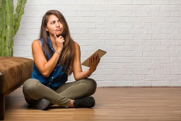 Retrato de la mujer latina joven que se sienta en el piso que piensa y que mira para arriba