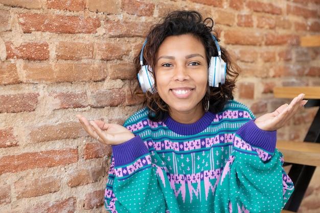 Retrato de una mujer latina sonriente. lleva unos auriculares y tiene las manos en alto. espacio para texto.