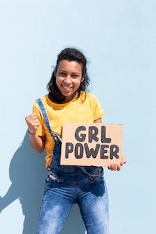 Retrato de una mujer latina sosteniendo una pancarta con el lema girl power