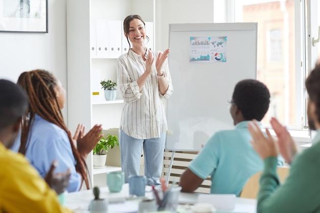 Retrato de mujer líder sonriente aplaudiendo mientras está de pie junto a la pizarra en la sala de conferencias y felicitando al equipo empresarial multiétnico por el lanzamiento exitoso