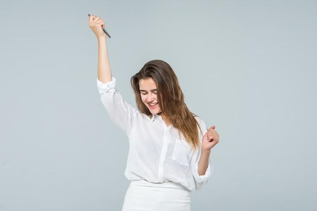 Retrato de una mujer linda alegre escuchando música en auriculares y bailando sobre un fondo blanco.