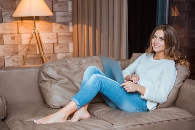 Retrato de una mujer linda feliz acostado con la computadora portátil en el sofá y mirando a la cámara