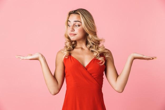 Retrato de una mujer linda hermosa confundida en vestido posando aislada sobre pared rosa mostrando copyspace