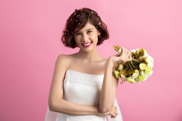 Retrato de una mujer linda juguetona sonriente que sostiene las flores aisladas en rosa