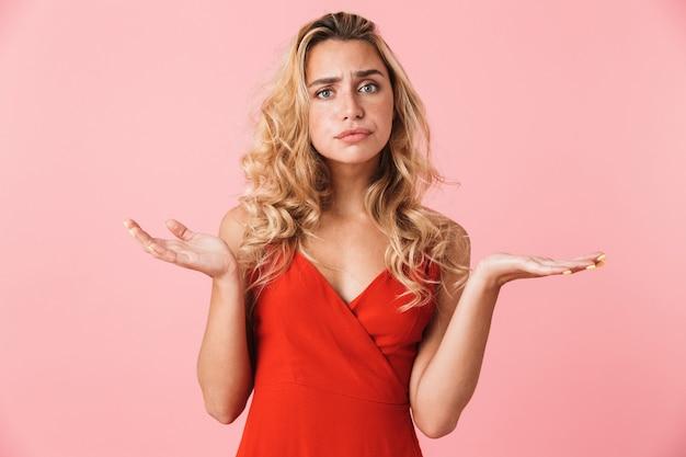 Retrato de una mujer linda rubia bastante joven descontenta confundida en vestido que presenta aislada sobre la pared rosada