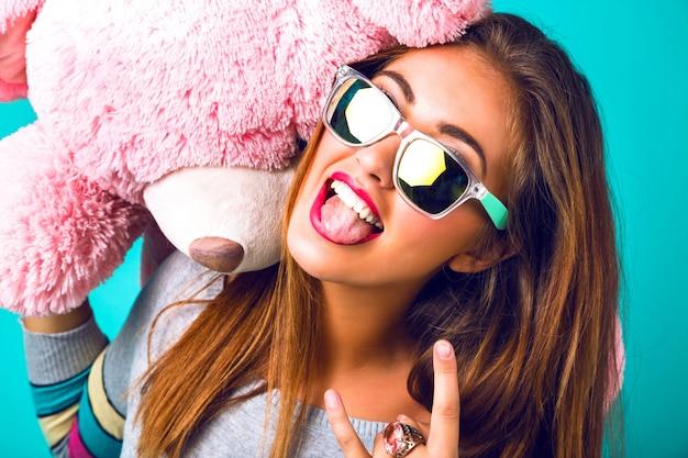 Retrato de mujer loca de cerca, divirtiéndose mostrando la lengua y sonriendo, gafas de sol espejadas, suéter brillante, sosteniendo un gran osito de peluche esponjoso.