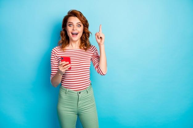 Retrato de mujer loca emocionada que usa una publicación de blog tipo teléfono celular piensa que los pensamientos tienen una idea increíble gritar wow dios mío, levantar el dedo índice, usar un jersey de moda aislado sobre color azul