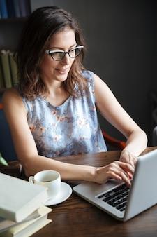 Retrato de una mujer madura en anteojos escribiendo en la computadora portátil