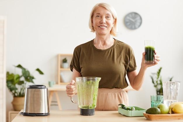 Retrato de mujer madura con cabello rubio sonriendo y bebiendo jugo de vegetales frescos mientras está de pie en la cocina