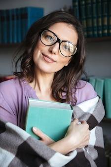 Retrato de una mujer madura cubierta en una manta con libro