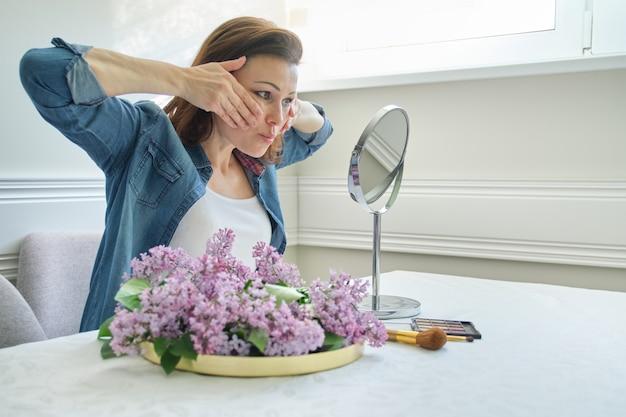 Retrato de mujer madura con espejo de maquillaje masajeando su cara y cuello