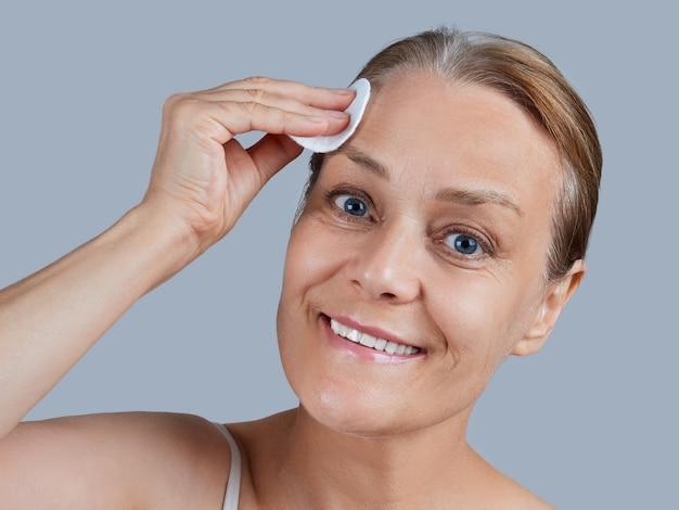 Retrato de una mujer madura con los hombros desnudos con un algodón. concepto de cuidado de la piel facial.