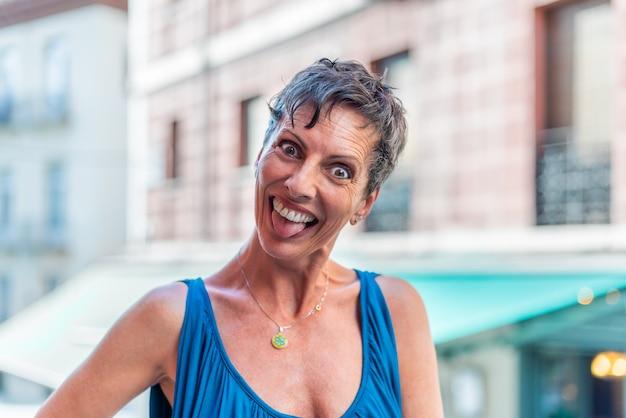 Retrato de una mujer madura de pelo corto divertido en la calle haciendo muecas. mujer de mediana edad en la ciudad divirtiéndose.