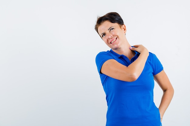 Retrato de mujer madura que sufre de dolor de cuello en camiseta azul y mirando cansado vista frontal