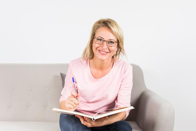 Retrato de la mujer madura sonriente con la pluma y el libro que se sientan en el sofá que mira la cámara