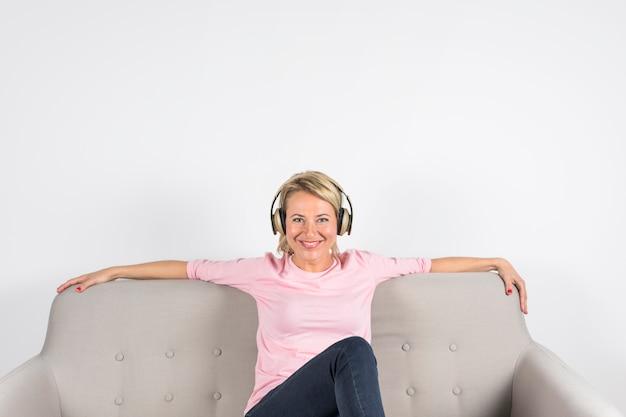 Retrato de una mujer madura sonriente que se sienta en el sofá que mira la cámara contra el fondo blanco