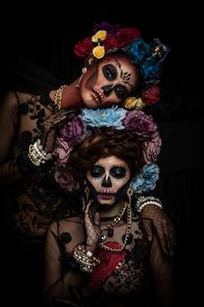 Retrato de mujer con maquillaje de calavera de azúcar vestida con corona de flores