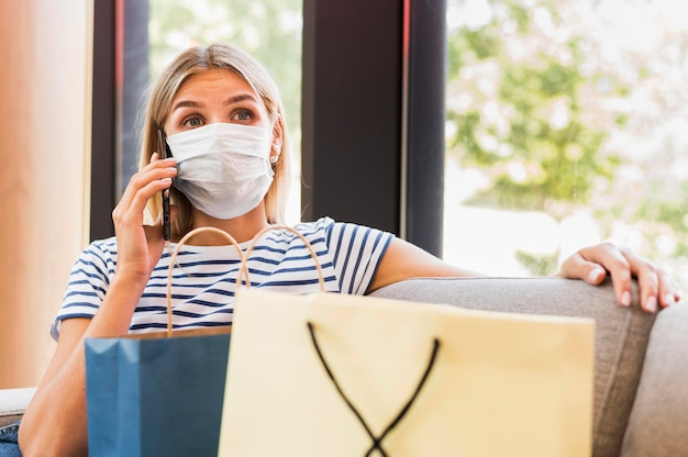 Retrato de mujer con mascarilla hablando por teléfono